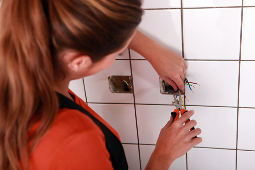 Female Electrician repairing socket inside of white wall