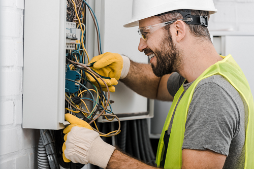 Smiling Technician wearing a Yellow safety Jacket, a grey tshirt, white safety hat and gloves inspecting an electrical panel